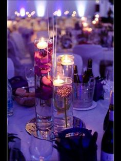 Trio cylinder vase with submerged flowers and floating candles placed on top of mirror tile and finished with scatter crystals
