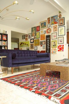 chic navy sofa, wall of art colorful artwork, & colorful, patterned ethnic rug all add up to a chic, happy, eclectic living room (dislike the coffee table, but c'est la vie)