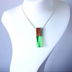 Geometric necklace - Resin jewelry  This green colored necklace is handcarved from transparent resin and is combined with exotic wood. The rectangular pendant would make for a great gift for a lady or a man. Polished to a high gloss, unique and one of a kind, this necklace will definitely get everyones attention. The pendant comes with a modern black jewelry box, perfect for gifting! We can also add a gift message, just let us know in note to seller when at checkout.  All of our products are…