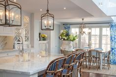 Chic cottage kitchen boasts tray ceiling Pottery Barn Gothic Lanterns illuminating white marble top island with farmhouse sink lined with blue French bistro barstools across from lit, glass-front cabinets flanking paneled range hood over high-end, gas range.