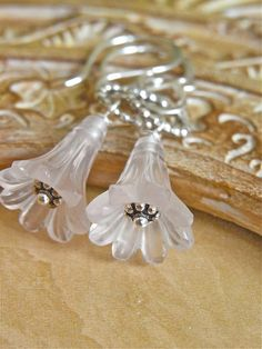 The Drosera earrings - delicate carved rose quartz flowers adorn these sweet earrings, completed with sterling silver.