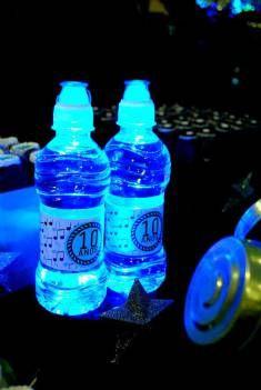 garrafinhas de água personalizadas com o tema da festa iluminadas de azul para esse aniversário balada cheio de detalhes neon para comemorar os 10 anos de um menino.