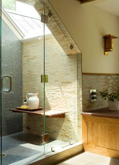 Showers tucked into dormers can feel cramped and cavelike, but adding a skylight can remedy the problem. This shower becomes a bright oasis, thanks to a generous skylight. Inside the shower, slate-blue glass tiles line the back wall and continue on the floor, giving the shower focal-point status. A textured stone tile was used on the sidewalls, as well as elsewhere in the bathroom, to unify the spaces.
