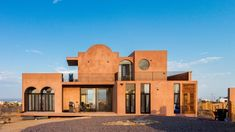 """A large terrace surrounds the home on the ground floor, and is slightly elevated to offer better views of its surroundings. The architect describes the cement-covered building as a """"monolithic sculpture"""". Concrete Cover, Rammed Earth Wall, Arch Doorway, Best Architects, Storey Homes, Thatched Roof, Mexico Vacation, Ground Floor Plan, Baja California"""