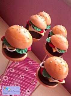 Estos cake pops son la mar de divertidos!!! Modelados en forma de hamburguesa...con su pan, carne, queso, tomate, lechuga, cebolla...no le falta un sólo detalle. ¿Y si además te decimos que está modelado sobre un delicioso bizcocho de chocolate cubierto de chocolate con leche?  Ñammmm ñaaaammm!!!! Buenísimosss