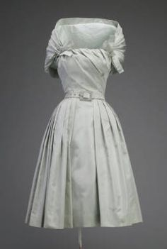 Cocktail dress, ca.1955. Silk taffeta. Christian Dior. The expertly draped bodice and attached shawl of this Christian Dior ready-to-wear cocktail dress are complex construction details usually found only in couture collections. These elements require a great deal of skilled labor usually considered too expensive for the ready-to-wear market.