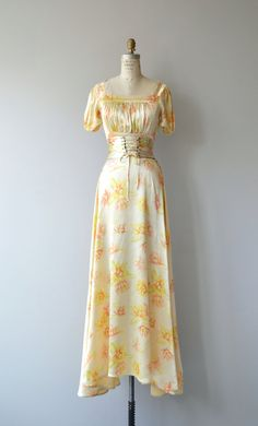 Vintage 1930s luminous yellow and peach floral silk satin gown with squared neckline, short sleeves, gathered bodice, fitted waist with matching corset laced belt backed in chocolate velvet, sweeping skirt and side snap closures. --- M E A S U R E M E N T S --- fits like: small bust: 32-34 waist: 26 hip: free length: 61 brand/maker: n/a condition: excellent ✩ layaway is available for this item To ensure a good fit, please read the sizing guide: http://www.etsy.com/...