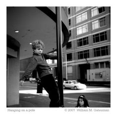 A kid hanging from a pole.