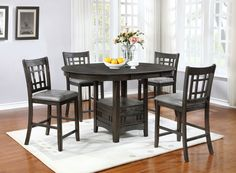 Extend an invitation to enjoy a meal at this Dana five-piece counter-height dining set. The 18-inch removable leaf allows you to grow the table for games or larger groups, or remove it to free up space in your kitchen or dining area. The table and chair frames are built from robust acacia and encased in matching, wire-brushed veneers. The result is a vintage and rustic look that will bring a bit of cabin glamour to your abode. Find additional storage within its pedestal base, helping you…