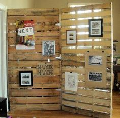 Pallet wall stained with Christmas photos throughout and garland on top in one of the corners for a different feel