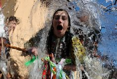 Young Slovaks dressed in traditional costumes throw a bucket of water at a girl as part of Easter celebrations in the village of Trencianska Tepla, 145 km north of Bratislava on April 9, 2012. (Photo by Samuel Kubani/AFP Photo)