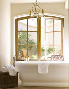I saw something similiar long ago- double wooden arched windows above a stand alone tub.  The other one had interior shutters as well.  So lovely