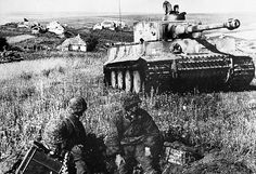 Three Waffen-SS soldiers in a foxhole watch as a Tiger 1 operating with the 2nd SS Panzer Division 'Das Reich' passes by during 1943