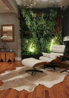 Trendy and cozy. Estar com poltrona Charles Eames em couro branco, tapete couro de vaca em tons claros, base neutra com paredes cinza, e parede verde linda!