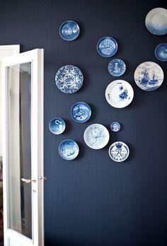 På væggen hænger platter fra forskellige årtier - ægte nostalgi med et moderne udtryk. Den assymetriske opsætning og den matte sortblå baggrund gør væggen ekstra stilfuld. Platterne er dels købt hos Royal Copenhagen, dels fundet på loppemarkeder.