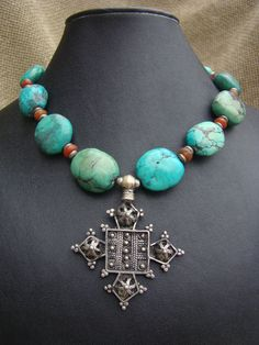 Necklace |  Nancy Sathre-Vogel.  An antique silver Ethiopian silver cross pendant is combined with contemporary  natural turquoise beads with carnelian spacer beads. | 250$