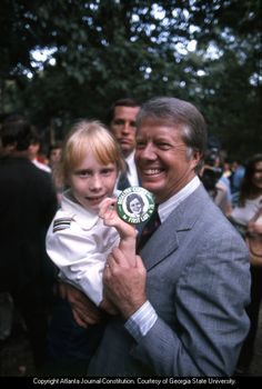 "Then-Governor and presidential hopeful Jimmy Carter and his daughter Amy hold up a ""Rosalynn Carter First Lady in button at the campaign kick-off in Warm Springs, GA, September"