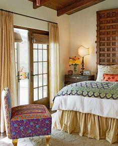 A carved  headboard and colorfully patterned textiles add an exotic element. Beautiful mix of patterns. The headboard is a reclaimed Indian carved panel.