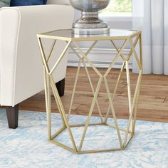 Whether you need it to rest movie night snacks or display your favorite decor, an end table should still add to your style. The perfect accent for luxe ensembles, this chic end table will instantly elevate your aesthetic. An antiqued mirrored top pairs with an open geometric base to round out this end table in chic style, while the sleek golden finish adds an extra pop of glam. Set it beside a clean-lined tufted sofa in your living room, then lean into the glamorous aesthetic by rolling out…