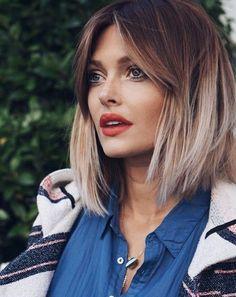 dunkelbrauner Ansatz und blonde Spitzen, Frisur mit Mittelscheitel, Haare mit grauen Spitzen, Frau mit eckigem Gesicht, gerader Nase und vollen Lippen, sie trägt orangefarbenen Lippenstift und hat große helle Augen, sie hat ein blaues Hemd und eine weiße Winterjacke mit Karomuster an