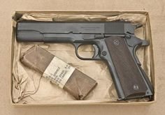 M1911A1 in the box with spare magazine wrapped in wax paper.