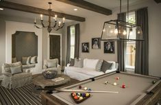 source: Thompson Custom Homes Family game room features clay colored walls and ceiling accented in rustic exposed wood beams. Candle chandelier over re-claimed wood round coffee table paired with white slipcovered sofa with gray linen pillows and white and gray zebra chairs over blue and brown striped rug. Game room with Restoration Hardware Filament Chandelier over pool table as well as built-in reading alcove.