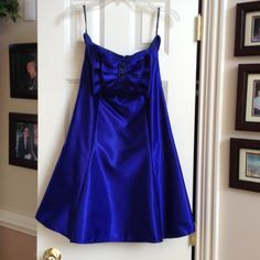 Electric Blue Strapless Formal This darling dress is made from Electric Blue Satin. It has a large Satin bow across the bust with blue and clear crystals in the center. There are 6 stays inside for support.Underneath the skirt is a black net attached slip to add fullness and under that is a blue satin lining. It zips up the back. This is a designer dress from Jessica McClintock. Jessica McClintock Dresses
