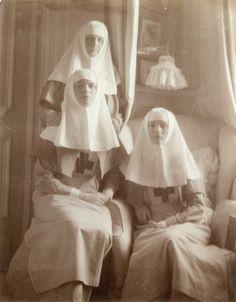 Empress Alexandra Feodorovna acompanhada por suas filhas as Grã-duquesas Olga Nikolaevna e Tatiana Nikolaevna, vestidas com o uniforme de enfermeiras, em Tsarskoe Selo, em 1915.
