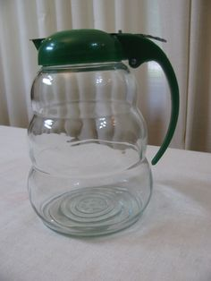 This vintage 1960s syrup dispenser or server has an interesting shape and a bright  green top with metal slide opener. Description from etsy.com. I searched for this on bing.com/images