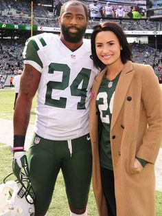Demi Lovato poses with Darrelle Revis at the New York Jets home game on Sunday at MetLife Stadium in East Rutherford, N.J.