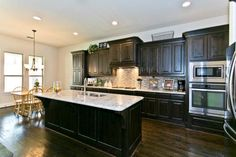 High contrast kitchen // Dark brown cabinetry, white granite countertops, stainless appliances