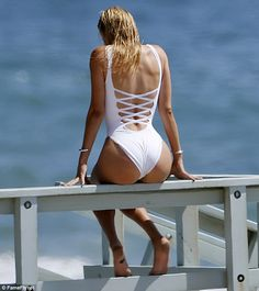 Bottoms up: Kelly also posed on a lifeguard tower in a white swimsuit with a lace-up style...