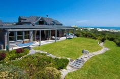 "Situated on one of the largest stands in Klein Slangkop Estate, this world-class landmark home overlooks the bay where Kommetjie and Noordhoek come together, and the whales frolic and play. Timeless in design, with the finest of imported materials and current technology, this is living as close to"" Paradise"" as possible."