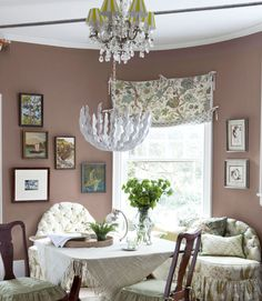 A custom banquette, designed to mimic the dining room's rounded wall, offers comfy seating. Jane inherited the table from her great-grandmother, and the chandelier is part of Stray Dog's new collection for West Elm.