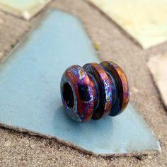 Titanium ribbed lanyard bead with blue smoke anodizing.