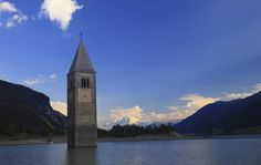 Church Tower - Lake Reschensee, South Tirol Province, Italy In 1950, a new dam meant flooding163 homes + a 14th century church.  Only the church tower remains above the water line, accessible on foot (or skates) when the lake freezes every winter.