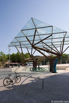 "CaixaForum entrance Barcelona, Spain Artist: Arata Isozaki, original architects Robert Luna, Robert Brufau, Jose Francisco Asarta bike rack with tree forms in the background About this project: Once a factory, this Art Noveau structure was converted into an center for art exhibits and other cultural events. A large scale sculpture by the entrance by Japanese architect Arta Isozaki consist of a tilted glass canopy supported by steel branches and square steel ""trunks""."