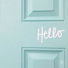 """Light pink """"Hello"""" vinyl quote word decal written in handwritten script is placed on the middle of a light green door."""