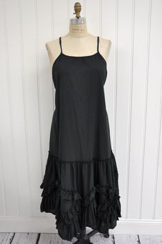 """Features:    Lovely long slip   Full hem   Raw edge ruffled detail along bottom   Skinny straps   Side ties   100%cotton voile, black   Fits sizes 2-18   Measurements:    Chest: about 50"""" around   Length: about 53"""" long"""