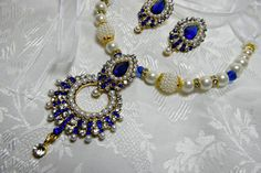 Art Deco necklace set, Gatsby necklace set, 1920s roaring 20s blue sapphire crystal pearl statement necklace set, great gatsby wedding, gatsby accessories, gatsby dress, gatsby party  Blue Sapphire: The Gem of Royalty, Art Deco, Gatsby 1920s era, design inspired. A Statement of Sophisticated Glamour.  The Beautiful blue sapphire austrian crystals shimmer amongst the faux off white pearls and rhinestone rhondels. gold plated embelishments. Attaches with a long delicate white organza ribbon…