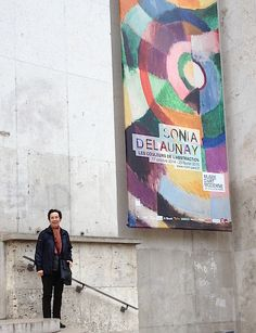 A Contemporary French Textile Odyssey. Author Barbara Shapiro with banner for Sonia Delaunay Exhibition at Museum of Modern Art, Paris 2014. Photo by Claude Cassoret