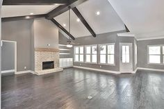 Gorgeous family room. I love grey walls, white trim & hardwood floors. This space is even more stunning with the brick fireplace, wood mantel…