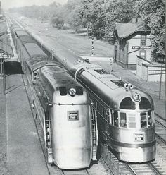 Streamlined Steam engine next to diesel electric early stage locomotive