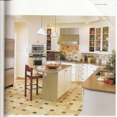 Interesting use of angles. wall cupboards as island, angled microwave over built-in oven leaves room for angled pantry of cleaning cupboard