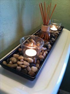 Cheap rocks from IKEA, a couple candles and a scented oil reed diffuser - cheap and easy (and yummy smelling) decor for the bathroom, fits perfectly on the back of the toilet...