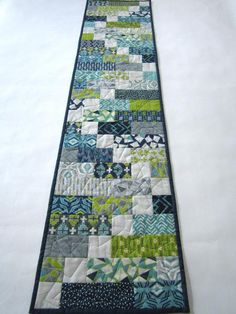 This modern table runner has blue, green and aqua colors in the fabrics. There is a light gray square that is in a zigzag format. I really like all the geometri