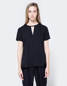 Simple top from Stelen in Navy. Split neckline. Narrow choker detail with concealed snap closure. Center seam down front. Stepped, curved hem.   • 100% polyester • Hand wash cold, dry flat