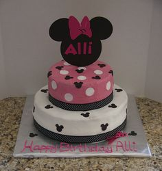 """Alli's Minnie Mouse Cake... Minnie Mouse Theme Birthday Party... I baked (2) 12' round cakes & (2) 8""""round cakes. Buttercream icing. The small Mickey Mouse heads are cut out of Edible Sugar Sheets with a Mickey Mouse punch. The topper is made with scrapbook paper cut out with Cricut using the Disney Mickey Font cartridge."""