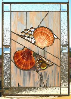 """Seashells and Nuggets by Reflections of Glass, (This beachy piece is an original design created with seashells and glass nuggets or globs.  It has brightly colored scallop shells, spiral shells with a beautiful cross-sectional design, and various tones of amber globs. The stained glass is a white-tan-clear wispy glass bordered by clear moss glass and 1 1/2"""" bevels. Framed in zinc, it measures 12""""x18"""" and is finished with a pewter patina) Stained Glass Designs, Stained Glass Panels, Stained Glass Projects, Stained Glass Patterns, Leaded Glass, Stained Glass Art, Mosaic Art, Mosaic Glass, Fused Glass"""