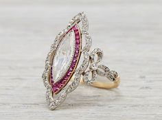 Edwardian ring made in platinum on gold and centered with an EGL certified .80 carat marquise cut diamond with F-G color and SI1 clarity. Accented with calibre cut rubies and single cut diamonds